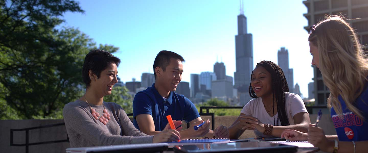 Students studying in a courtyard on a clear day with the Chicago skyline in the background.